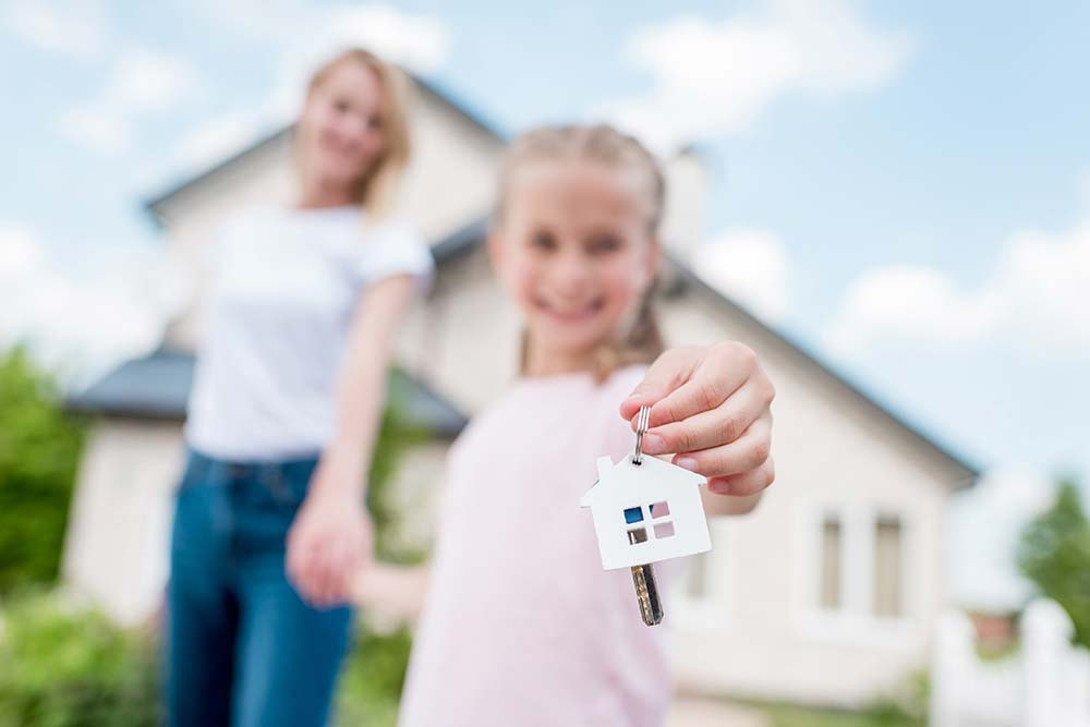Mother and daughter holding the keys to their new house after a home inspection