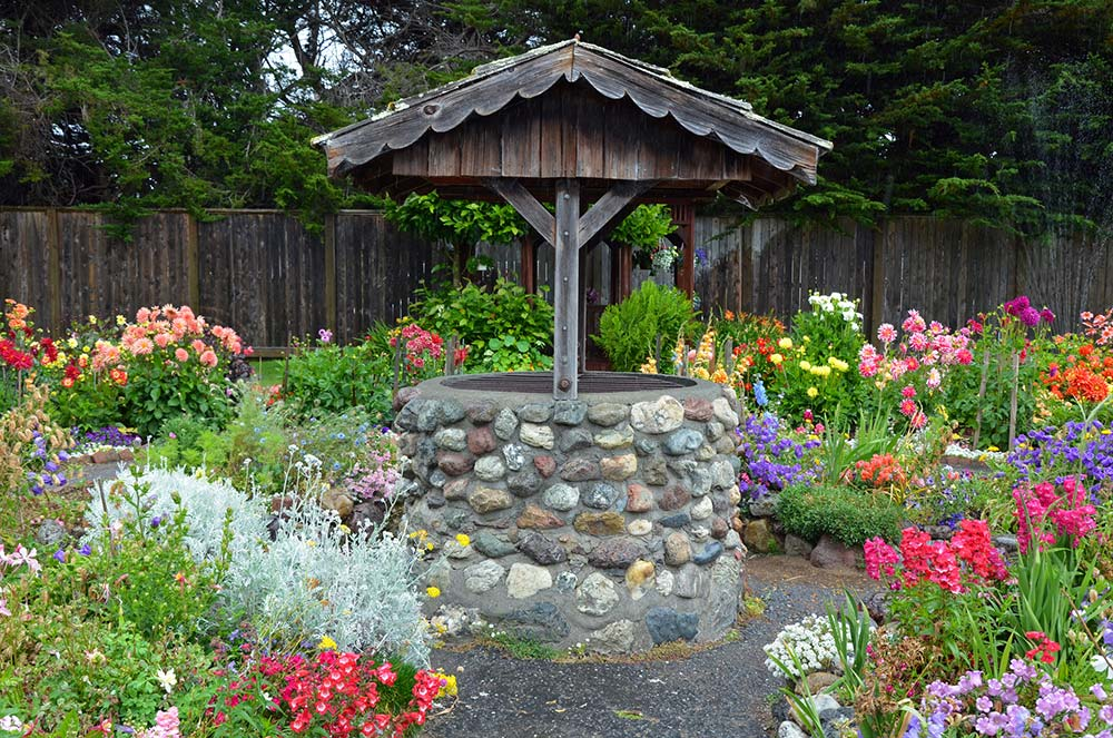 Old brick wishing well in colorful dahlia garden while preforming home inspection services